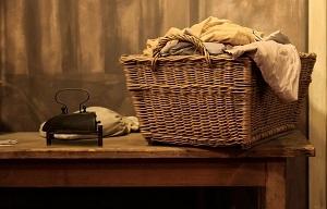 Ein Wäschekorb auf einem Tisch mit Leintüchern drinnen.